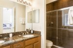 The master bathroom has dual sinks and a walk in tile shower