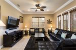 The living area has ample seating for everyone to enjoy the large wall mounted flat screen TV