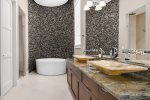 The master bath has a gorgeous custom rock wall with large soaking tub and his and hers sink basins