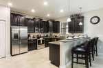 The full kitchen has stainless steel appliances, granite counters and breakfast bar seating for 4