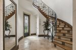 The spiral staircase with gorgeous ironwork details highlights the chandelier and wood beams