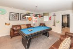 The second floor loft has a pool table and comfortable seating for an additional games area