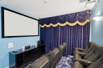The theater room has a large projection screen, surround sound and stadium style seating