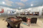 The aviation themed games room features a foosball table, 3 X 47-inch SMART TVs that can connect to the Xbox One, and PlayStation 4