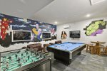 Featuring a foosball table, pool table, gaming system and table and chairs