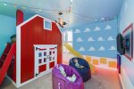 Custom built twin bunk beds with a slide, TV and seating in this fun kids room