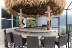 Tiki bar with BBQ grill, TV, and fridge