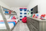 An upstairs bedroom with a twin/full bunk bed with some super decorations