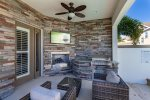 Hang out underneath the covered lanai with a summer kitchen, fireplace,  outdoor TV and plush patio furniture