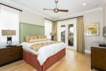 Upstairs master bedroom with plush king size bed, wall mounted TV and private en-suite bath