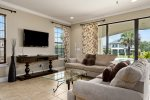 Plush couches surrounding the TV and with easy access to the patio area