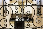 Wrought iron gates subtly separate the side nook with an extra sink, cabinets, wine rack, and mini fridge