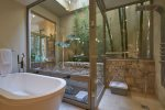 Spacious master bath with soaking tub and a shower that opens to a calming outdoor stepping fountain