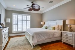 Master Bedroom has a king bed, TV and ceiling fan.