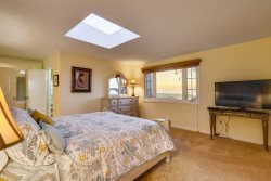 1st master bdrm has a king bed, ocean view, skylight and TV.