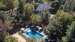 An aerial view of the house and pool. Beautifully situated and landscaped, the pool 4-feet deep, 45-feet long spa, and surrounding deck has a table for 6, lounge chairs, gliders, 6 umbrellas, a gas BBQ, fridge and changing room with sink and toilet.