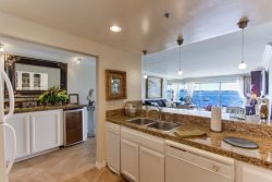 Kitchen open to bay view and wet bar with mini fridge for beverages.