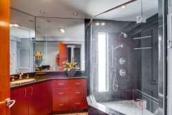 Custom bathroom with granite counters, tiled floor, and a large walk-in shower