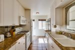Fully Equipped Kitchen with Granite Counters and White Cabinets