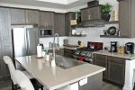 Gourmet Chefs Kitchen with Stainless Steel Appliances and Quarts Countertops