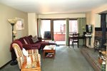 Mammoth Condo Rental Wildrose 9: Living room with wood burning stove and access to outdoor deck