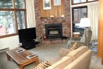 Mammoth Lakes Rental Woodlands 30 - Living Room with a Woodburning  Stove and Access to an Outdoor Deck