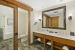 Double stone vanity, and separate water closet with sliding barn type door for privacy