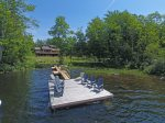 Large dock with lounge chairs and room for a boat and kayaks