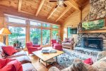 Main level Great Room with TV, wood burning fireplace, access to the deck and views of Megunticook Lake