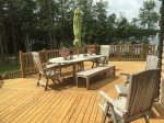 Ample outdoor furniture on the upper deck, lower patio, and picnic tables in the field as well as a firepit with chairs shoreside