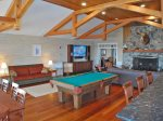 Main Lodge Room with billiard table, shuffleboard, large stone fireplace and sitting area