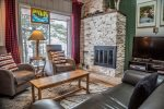 The living room features stone fireplace and large flat screen TV