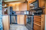 The well-stocked kitchen offers modern stainless steel appliances.
