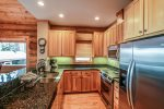 The fully equipped kitchen has granite countertops and high-end stainless steel appliances.