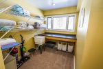 The laundry room has a folding table and plenty of space for folding laundry.