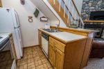 The kitchen is small but well equipped with full sized appliances and a dishwasher.