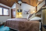 Though it`s in a sleeping loft, this master bedroom has plenty of privacy thanks to a glassed in window looking down over the living room and a pocket door at the staircase.