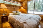 The bedroom has a queen bed and more large windows to allow guests to enjoy the views of the north woods.