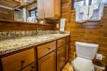 The bathroom features the same quality cabinetry and granite countertops found in the kitchen.