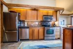 The galley style kitchen has granite countertops and stainless steel appliances.