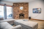 The lower level living area features a Roku TV and wood burning fireplace.