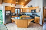 The kitchen features newer appliances and a large island for preparing meals.