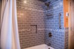The bathroom features a custom tile-surround shower/tub combo.
