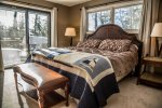 The master bedroom features a king sized bed and a step-out to the lake-facing deck.