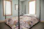 The main level bedroom is located off of the dining area and features a queen sized bed.