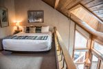 The master bedroom is located in the loft area and is open to the living area below.