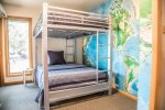 The first guest bedroom has full over full bunk beds and features a map of the world.