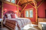 The timber frame master bedroom features a queen bed and electric fireplace.