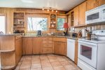 The kitchen features full sized appliances and granite counters- perfect for preparing a home cooked meal during your stay.