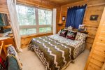 The first bedroom has a queen bed, TV, and great Devil Track Lake views.